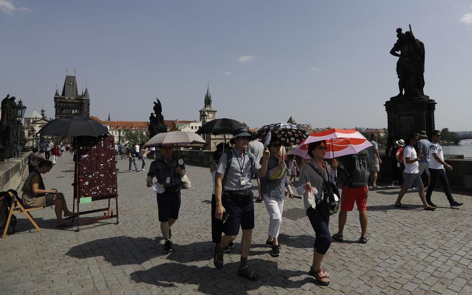 d451e750 Turister i Prag använder paraplyer för att skydda sig mot solen. Bild: Petr  David Josek